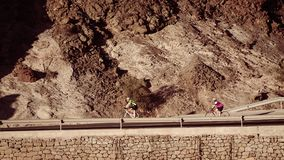 Couple cyclists are riding down on mountains road.  royalty free stock photography