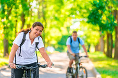 Couple of cyclists riding in park Royalty Free Stock Images