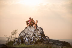Couple cyclists sitting on stone near bicycles in the evening Stock Photos