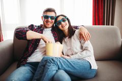 Couple in 3D glasses watch tv with popcorn. Smiling couple in 3D glasses sitting on couch and watch tv with popcorn at home, men with remote control in hand royalty free stock images