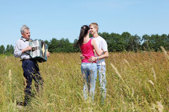 Couple dance near grandfather plays on accordion. Young couple dance near grandfather plays on accordion near wood in field royalty free illustration