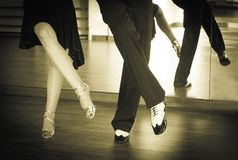 Male and female legs dancing latin rhythms and swing. Couple of dancers dancing lindy hop in bright gold and black and white shoes Royalty Free Stock Images