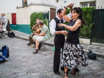 Couple dances to street musicians' jazz on Montmartre in Paris. Formally dressed couple in foreground dances to street jazz musicians - guitar and fiddle - in Royalty Free Stock Images