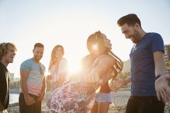 Couple dancing on beach partying with friends. Portrait of couple dancing on beach partying with friends Royalty Free Stock Images