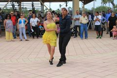 Couple dancing at a festival in Miami. Couple performing in traditional dress dancing salsa in front of crowd at a rodeo festival in Miami, Florida. outdoors Stock Images