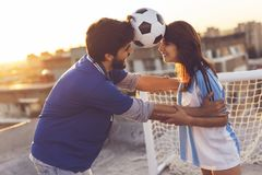 Couple dancing with a football between their heads stock image