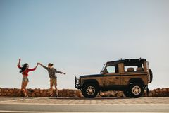 Couple dancing in front of their car. Man and women enjoying a summer vacation road trip royalty free stock image