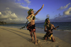 Couple dancing hula. Young couple dancing hula on the beach at sunrise in Hawaii with ukulele stock images