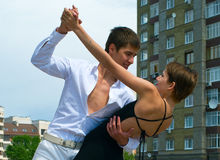 Couple dancing Latino dance. Young couple dancing Latino dance against urban landscape Stock Image