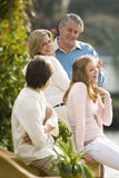 Couple dancing and looking at kids. Mature couple dancing outdoors, looking lovingly at daughter and son in foreground Stock Photos