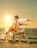 Couple dancing near the ocean. Young couple dancing near the ocean at sunset Stock Photos