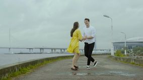 Couple dancing rock-n-roll dance together at the embankment after the rain. stock footage