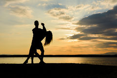 A couple dancing salsa by the sea at sunset stock photo