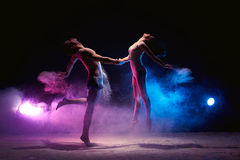 Couple dancing on the scene in cloud of powder. Contemporary art - full length shot of young graceful dance couple  performing in dark studio or scene in cloud Stock Image