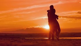 Couple dancing a slow dance in sunset sun silhouettes, Valentine`s Day a man and a woman stock footage