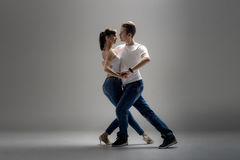 Couple dancing social danse. Beauty couple dancing social danse  kizomba or bachata or semba or taraxia , on grey background Royalty Free Stock Photos