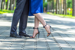 Couple dancing  in the street. Couple dancing in the street at sunny day.Blue color dress woman and man in suite, close up legs Stock Photos