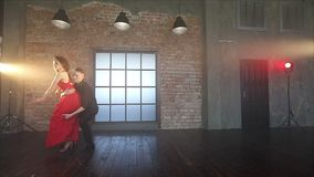 Couple dancing tango in retro room. A young man in black clothes and an attractive woman in a red dress rehearse dancing in the studio. Slow motion 100 fps stock footage