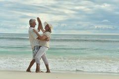 Couple  dancing  on  tropical beach. Happy elderly  couple  dancing  on  tropical beach Royalty Free Stock Photos