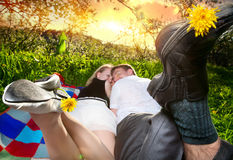 Couple with dandelions. Young beautiful couple lying on blanket around green grass and holding dandelions by their legs at sunset sky background Royalty Free Stock Image