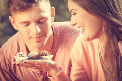 Couple on date with cupcakes. Love and dating. Attractive women giving cupcakes cookies to handsome man. Happy cute lovers on date outdoor Stock Images