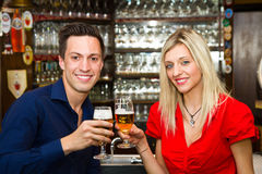 Couple on a date enjoying their drink in a pub. Young couple on a date enjoying their drink in a pub Stock Photos