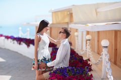 A couple on a date. Happy lovers. A romantic couple on a resort background. Young lovers near colorful flowers. Tourism concept. royalty free stock photo