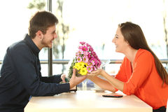 Couple date with man giving flowers. Profile of a couple dating and looking each other with a men giving a bouquet of flowers to his partner in a coffee shop Royalty Free Stock Photography