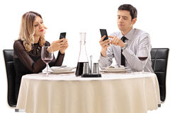 Couple on a date playing with their phones Stock Images