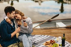 Couple on a date sitting together beside a lake drinking wine. Romantic couple on a date sitting beside a lake with snacks and wine. Happy women sitting with her royalty free stock photo
