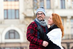 City Couple date on street on urban background. Happy guy in glasses with girl in season wear. Urban rouge hair woman hugging man stock photo