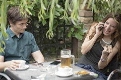 Couple on a date, woman talking too much. Young men is bored and stressed with his companion having too much fun on the phone, ignoring him completely royalty free stock photos