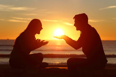 Couple dating falling in love at sunset. Portrait of a side view of couple or friends silhouette dating and falling in love with a boyfriend giving the sun to stock image