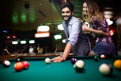 Couple dating, flirting and playing billiard in a pub. Couple dating, flirting and playing billiard in a pool hall royalty free stock photos