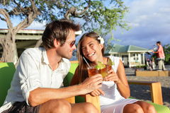 Couple dating having fun drinking alcohol on beach. Couple dating having fun drinking alcohol at beach club with alcoholic drink beverage Mai Tai cocktail on royalty free stock photography