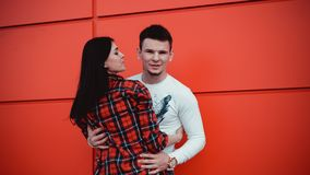 Couple dating and hugging in love in a sunny day - red background. Couple dating and hugging in love in an urban in a sunny day - red background royalty free stock images