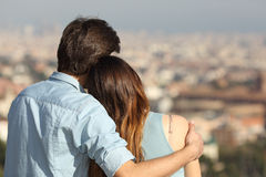 Couple dating in love and hugging watching the city. Back view of a couple dating in love hugging and looking the city in a sunny day Stock Image
