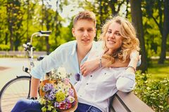 A couple on a dating in a summer park. Attractive young couple on a dating in a summer park royalty free stock image