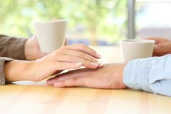 Couple dating and touching hands. Close up of a couple dating and touching hands in a bar or house Stock Image