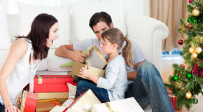 Couple and daughter unwrapping Christmas presents Stock Images