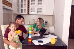 Couple with daughter working from home using laptop stock image