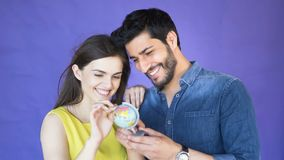 Couple decides on trip. Smiling young couple deciding on a country to visit as looking around the small globe, handsome asian man in blue denim shirt holding stock video footage
