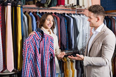 Couple deciding on new shirt in men's cloths store Royalty Free Stock Photography