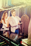 Couple deciding on new suit in men's cloths store Royalty Free Stock Photos