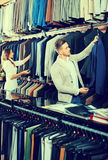 Couple deciding on new suit in men's cloths store Royalty Free Stock Photography
