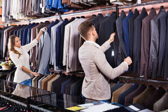 Couple deciding on new suit in men's cloths store Stock Photos