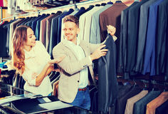 Couple deciding on new suit in men's cloths store Stock Images