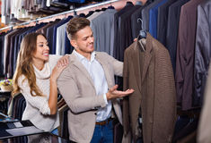 Couple deciding on new suit in men's cloths store Royalty Free Stock Image