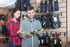 Couple deciding on protective gloves. Happy young loving couple deciding on protective gloves in sports clothes store Stock Image