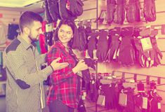 Couple deciding on protective gloves. Young loving couple deciding on protective gloves in sports clothes store Stock Image